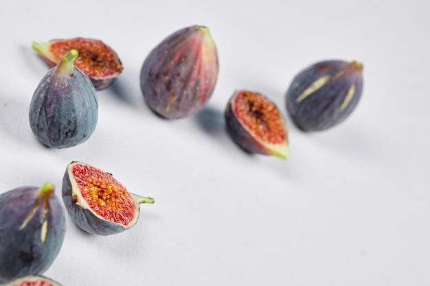 Figi całe i plastry fig na białym tle.