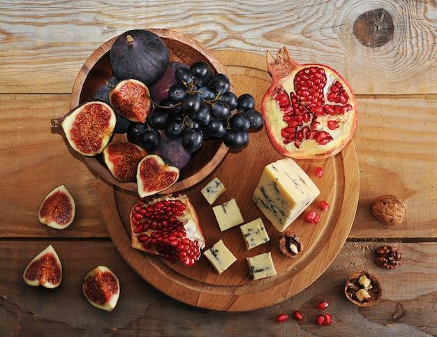 Figi i czarne winogrona w drewnianej misce