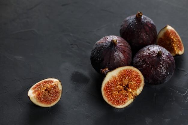 Figi i plastry fig na ciemnoszarym tle. fotografia ciemnych potraw.