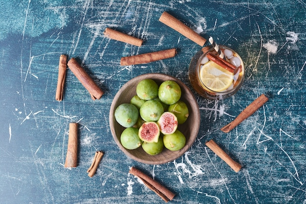 Figi i przyprawy przy filiżance napoju na niebiesko.