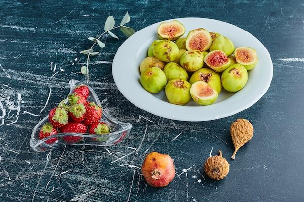 Figi na białym talerzu z truskawkami w szklanej filiżance.