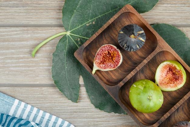 Figi w drewnianym talerzu na zielonych liściach.