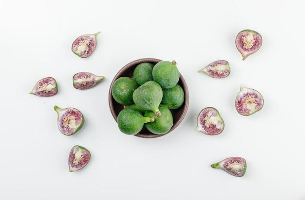 Figi w glinianej misce z plasterkami widok z góry na białej ścianie