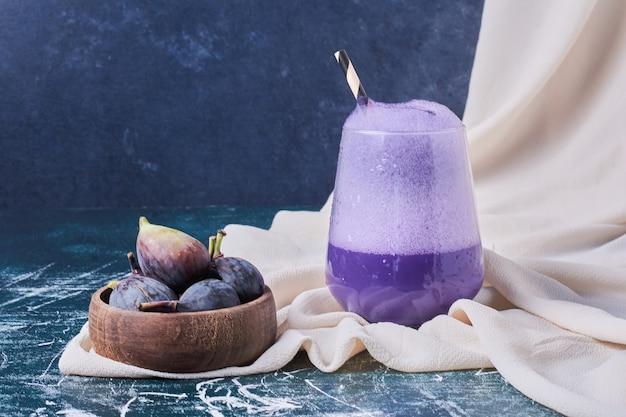 Figi w misce z filiżanką napoju na niebiesko.