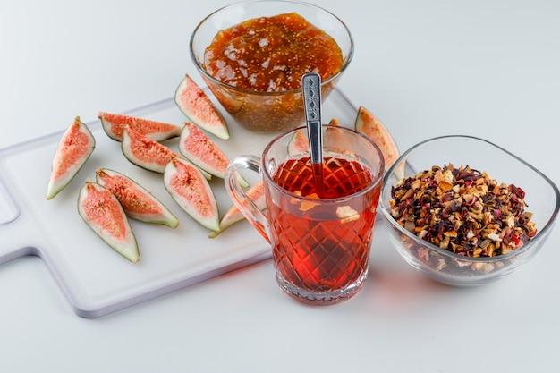 Figi z dżemem figowym, herbatą, łyżeczką, suszonymi ziołami na białej i deską do krojenia, widok z wysokiego kąta.