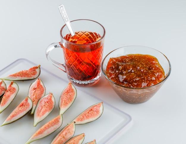 Figi z dżemem figowym, herbatą ziołową, łyżeczką pod dużym kątem na białym i deską do krojenia