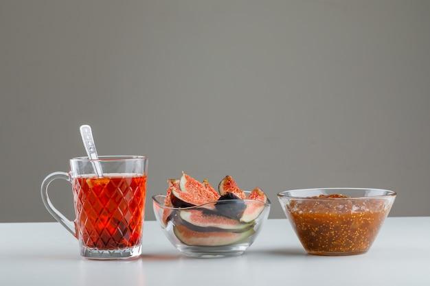 Figi z dżemem figowym, herbatą ziołową, łyżeczką w misce na białym i szarym, widok z boku.