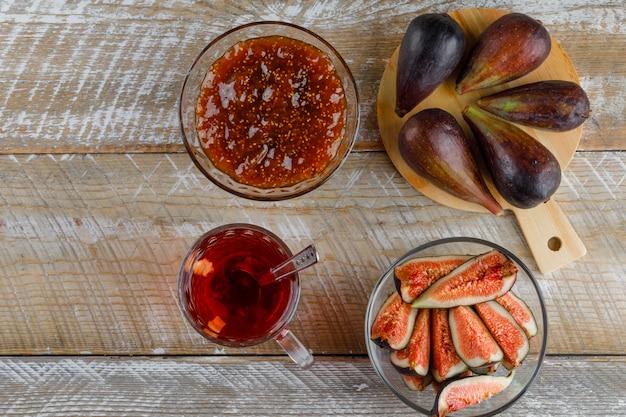 Figi z herbatą, dżemem figowym, łyżeczką w misce na desce do krojenia i drewnianej, płasko ułożone.