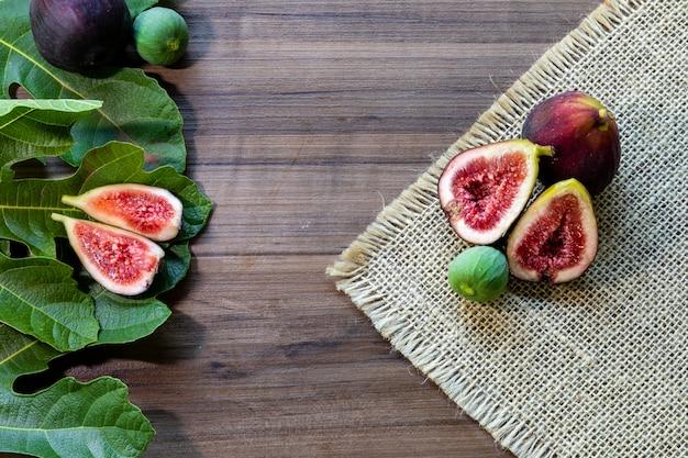 Figi, zielone liście na rustykalnym drewnianym stole