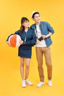 Figlarna azjatycka para w letnich ubraniach na co dzień z akcesoriami plażowymi studio strzał na białym tle na żółtym tle