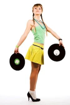 Figlarna blond dziewczyna z płytami winylowymi na białym