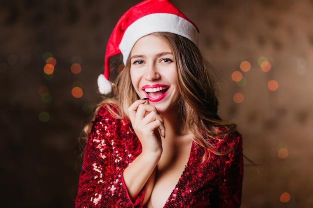 Figlarna brunetka kobieta o ciemnych oczach pozuje w kapeluszu świętego mikołaja z pięknym uśmiechem na błyszczącej ścianie