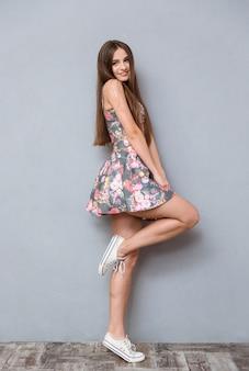Figlarna, całkiem szczęśliwa uśmiechnięta młoda kobieta z długimi włosami w kwiecistej sukience i tenisówkach pozuje na jednej nodze