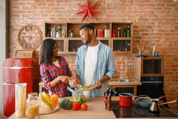 Figlarna czarna para gotuje obiad w kuchni