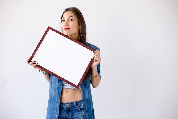Figlarna dziewczyna trzyma pusty biały plakat lub plakat