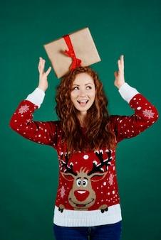 Figlarna dziewczyna z prezentem świątecznym patrząc na miejsce