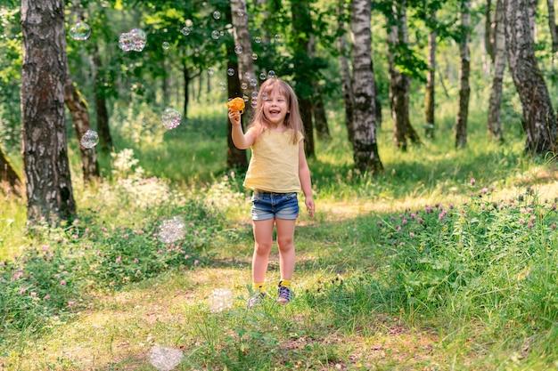 Figlarna dziewczynka dmuchająca bąbelkami z pistoletu-zabawki w letni słoneczny dzień