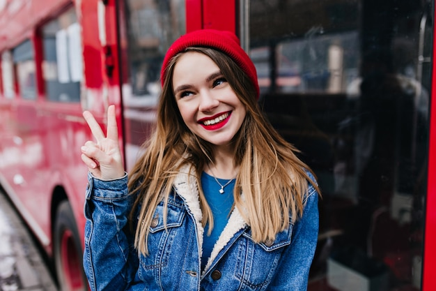 Figlarna dziewczynka kaukaski z modną fryzurą pozującą ze znakiem pokoju. odkryty strzał pięknej kobiety w dżinsowej kurtce, śmiejąc się podczas sesji zdjęciowej.