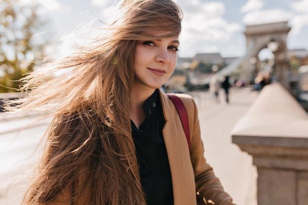Figlarna jasnowłosa kobieta w beżowej kurtce spaceru na świeżym powietrzu w wietrzny dzień