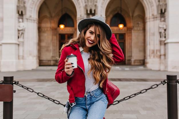 Figlarna kobieta w dorywczo czerwonej kurtce pozuje przed starym muzeum z filiżanką kawy