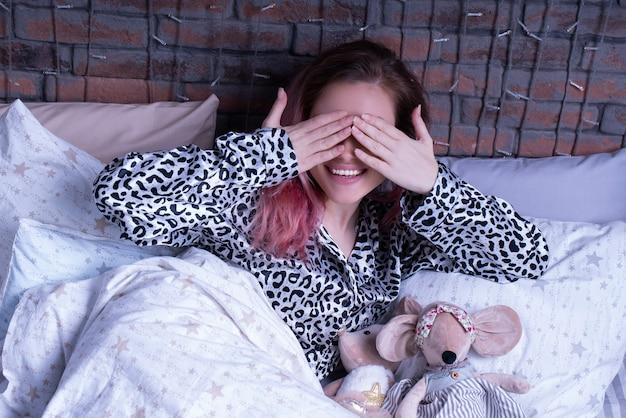 Figlarna kobieta w lampartowej piżamie zakryła oczy dłońmi