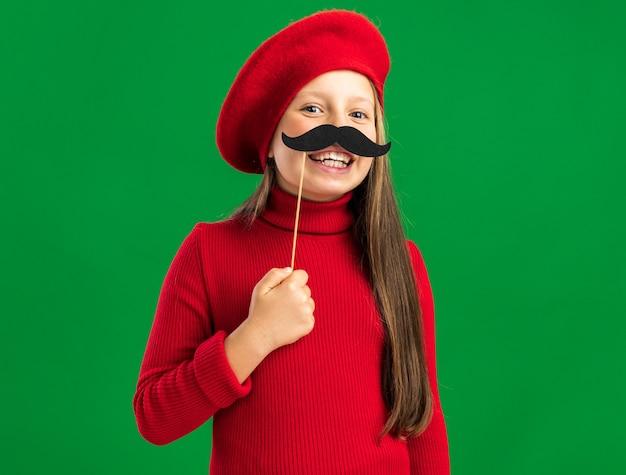 Figlarna mała blondynka ubrana w czerwony beret, próbująca fałszywych wąsów, patrząc na przód na zielonej ścianie z miejscem na kopię