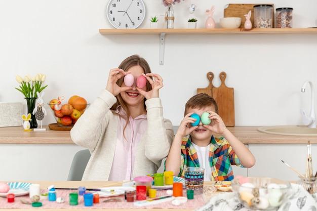 Figlarna mama i syn zakrywają oczy malowanymi jajkami
