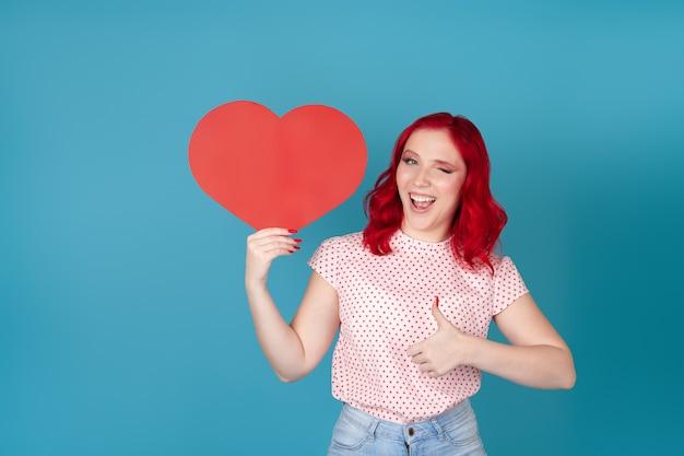 Figlarna młoda kobieta z czerwonymi włosami, trzymając czerwone papierowe serce, mrugając i pokazując kciuki do góry