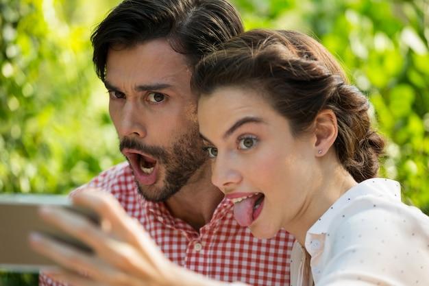 Figlarna młoda para biorąc slefie przez telefon komórkowy w parku