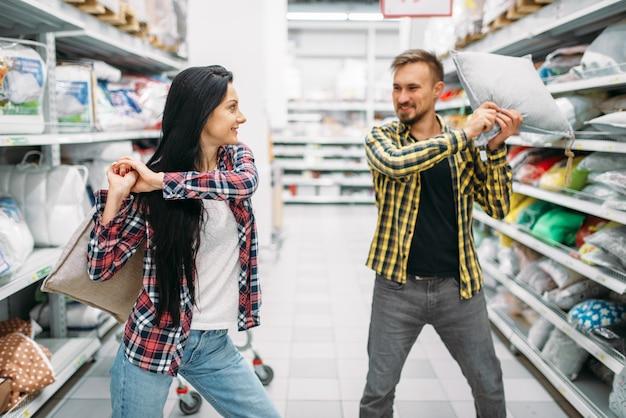 Figlarna para w supermarkecie, walka na poduszki. klienci płci męskiej i żeńskiej na rodzinne zakupy. mężczyzna i kobieta kupują towary do domu