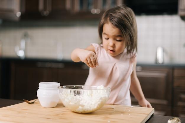 Figlarna piękna dziewczynka bierze sól z solniczki palcami, aby dodać ją do ciasta