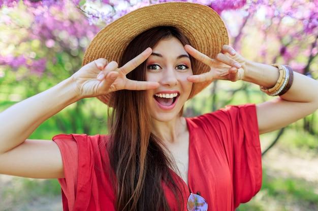 Figlarna śliczna dziewczyna robi śmieszną minę i pokazuje znaki, pozuje w wiosennym parku na kwitnących drzewach
