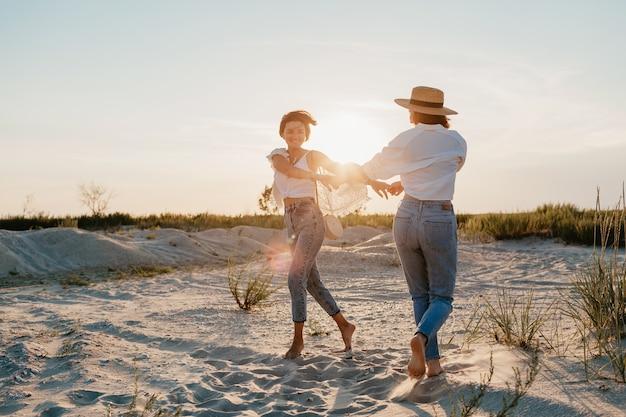 Figlarne dwie młode kobiety bawiące się na plaży o zachodzie słońca, homoseksualne lesbijki kochają romans
