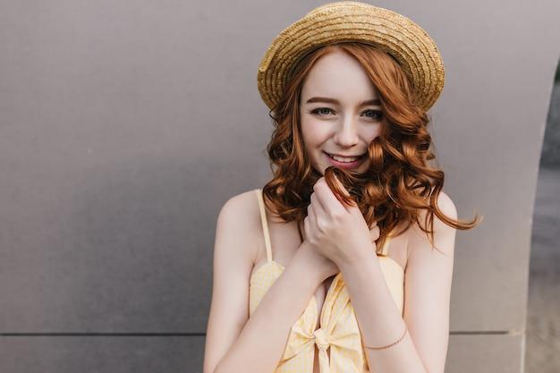 Figlarnie biała dziewczyna w kapeluszu uśmiecha się na szarej ścianie i patrzy. portret dobrego humoru modelki dotykając jej rude włosy.