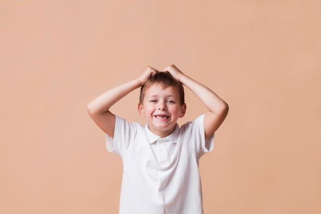 Figlarnie chłopiec patrzeje kamerę na prostym tle z jego pięknym uśmiechem