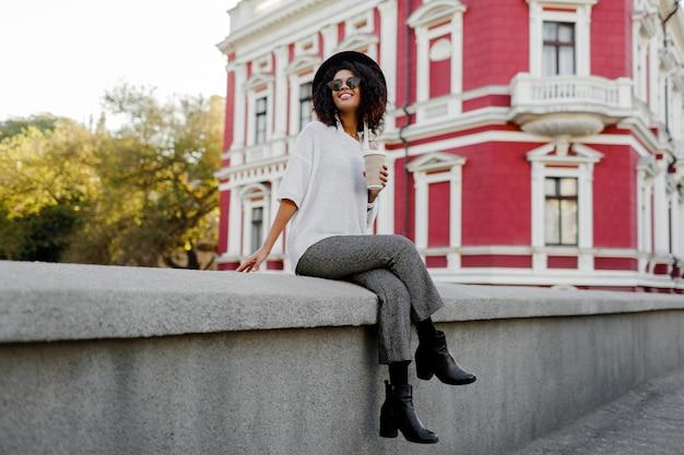 Figlarnie czarna kobieta z włosami afro siedzi na moście i dobrze się bawi. na sobie skórzane buty i modne spodnie. nastrój w podróży. szczęśliwy czas wolny w starym europejskim mieście.