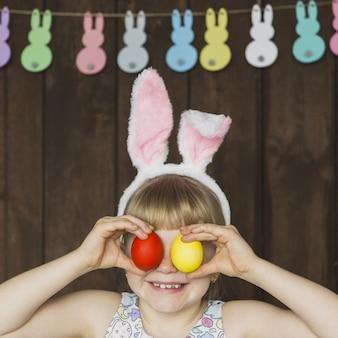 Figlarnie dziewczyna pozuje z barwionymi jajkami