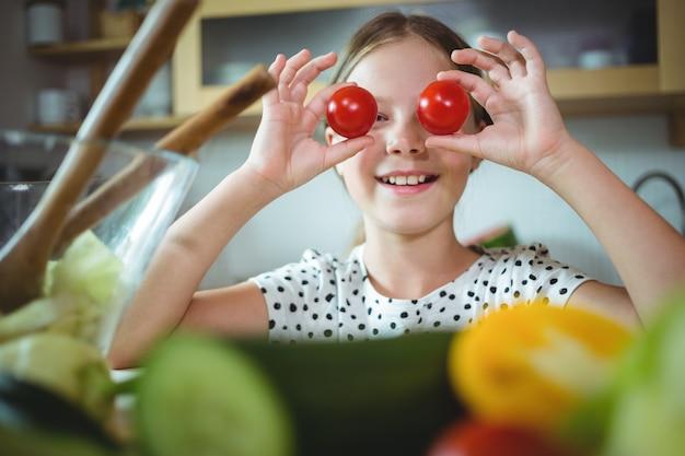 Figlarnie dziewczyna trzyma czereśniowego pomidoru na jej oku
