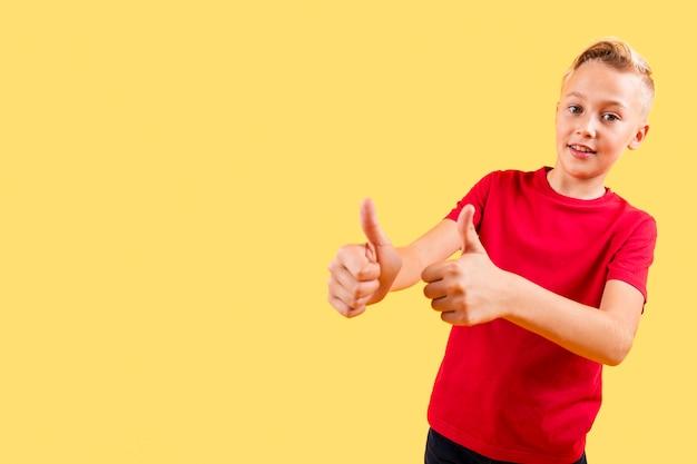 Figlarnie młoda chłopiec pokazuje ok znaka z przestrzenią