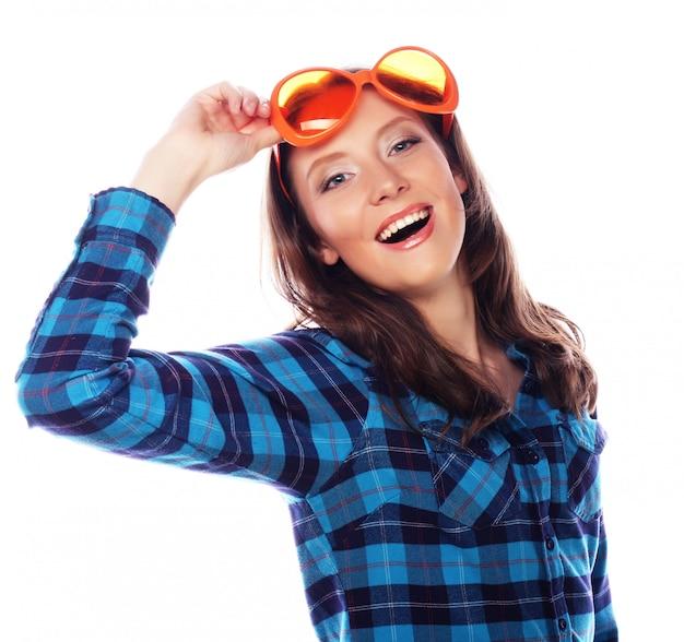 Figlarnie młoda kobieta z dużymi partyjnymi szkłami.