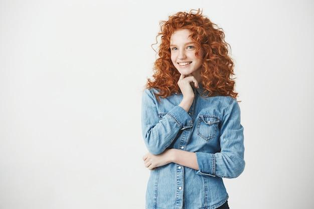 Figlarnie piękna rudzielec dziewczyna uśmiecha się kopii przestrzeń.
