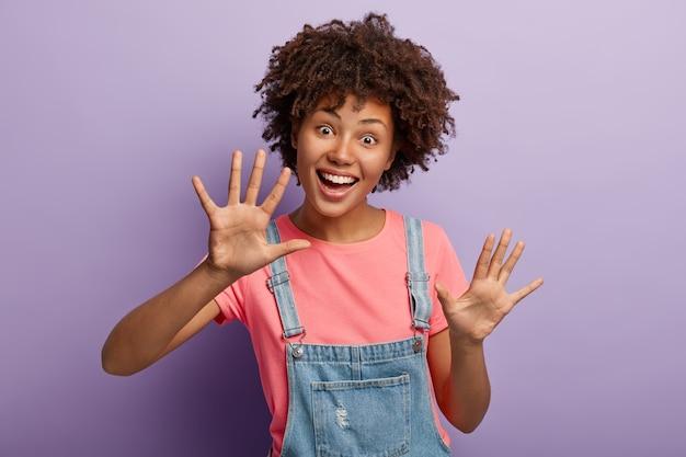 Figlarnie rozbawiona ciemnoskóra kobieta pokazuje dłonie do kamery, ma fryzurę afro, ma radosny wyraz twarzy