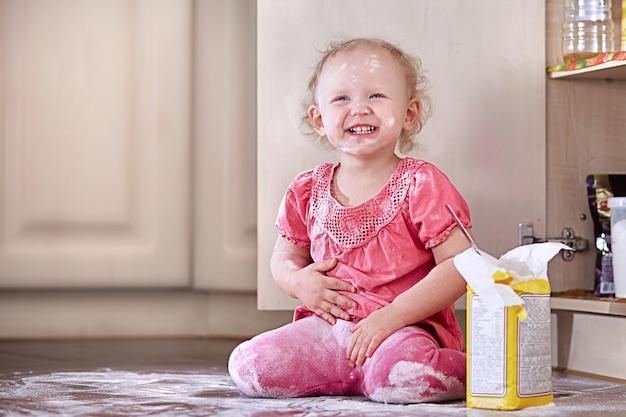 Figlarnie roześmiana dziewczynka posmarowana mąką siedzi na podłodze w kuchni. skopiuj miejsce.