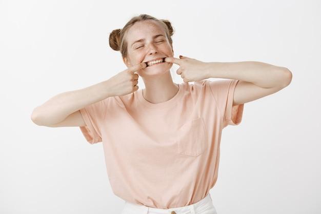 Figlarnie śliczna nastolatka pozuje na białej ścianie