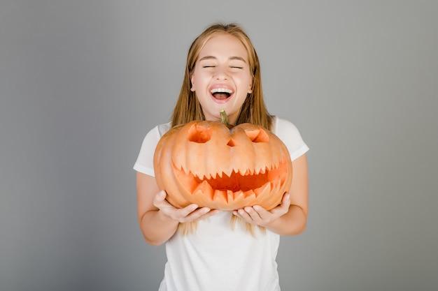 Figlarnie śmieszna blondynki dziewczyna z halloweenową jack o latarnią dynią odizolowywającą nad popielatym