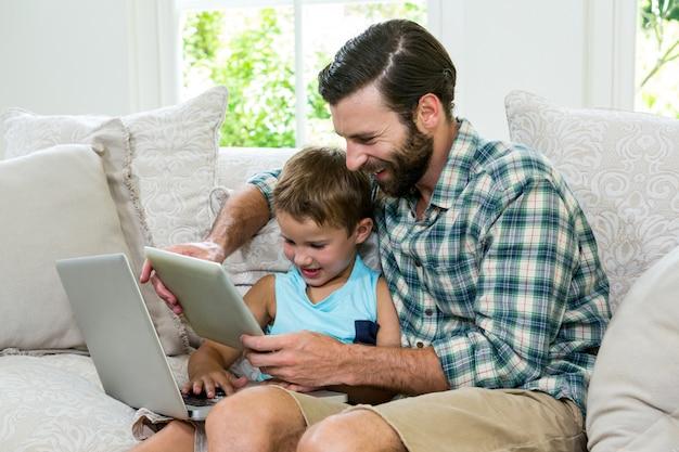 Figlarnie syn i ojciec z laptopem i cyfrową pastylką na kanapie