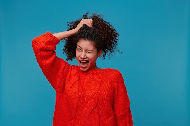 Figlarnie uśmiechnięta kobieta ubrana w czerwony sweter z radosną śliczną buźką i uśmiechnięta