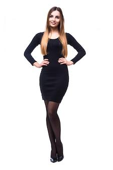 Figlarnie zabawna kobieta stojąca w czarnej sukni na białym tle w całym ciele