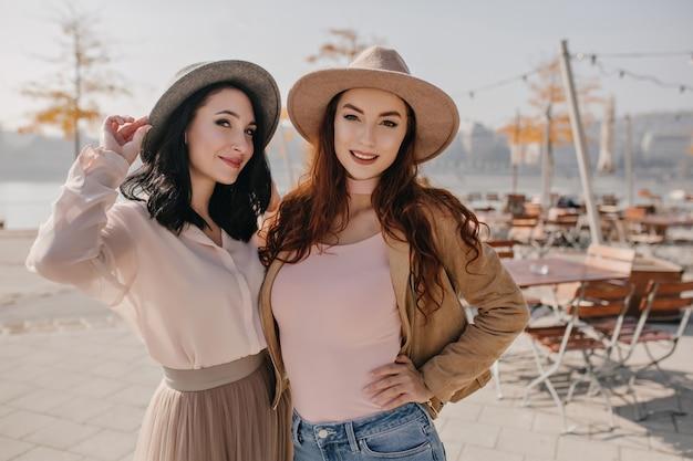 Figlarny brunetka kobieta w długiej spódnicy uśmiecha się z imbirową siostrą