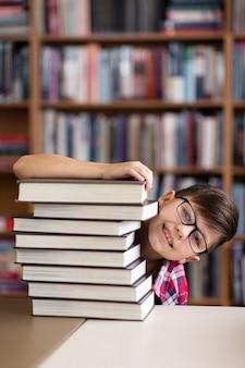 Figlarny chłopiec chowający się za stos książek